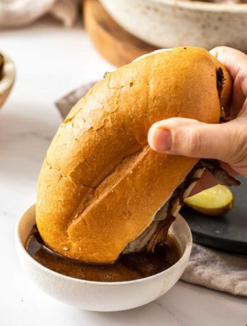 french dip sandwich in bowl of au jus