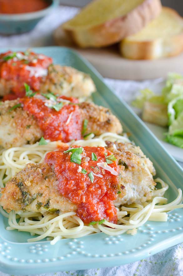 Three plated chicken breasts over spaghetti with marinara sauce.