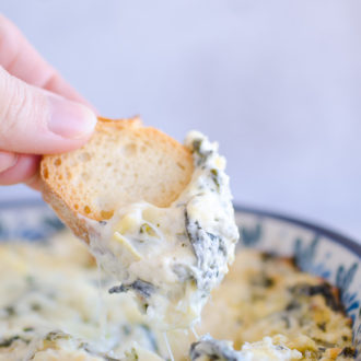 baguette dipped into spinach artichoke dip