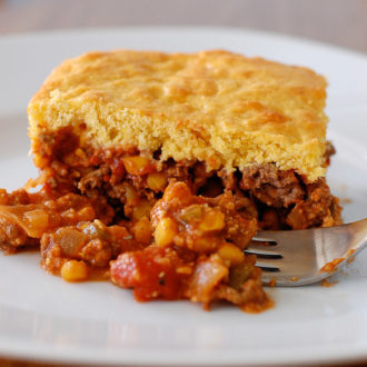 Beef casserole with cornbread topping on a plate with fork