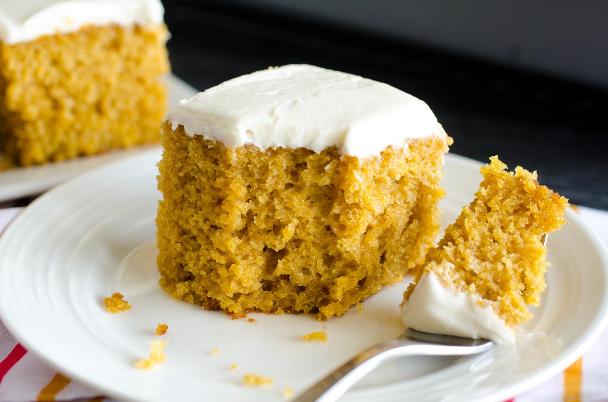 bite out of pumpkin bar with cream cheese frosting on round plate with fork