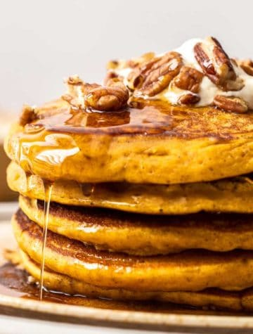 stack of pumpkin spice pancakes with maple syrup and pecans