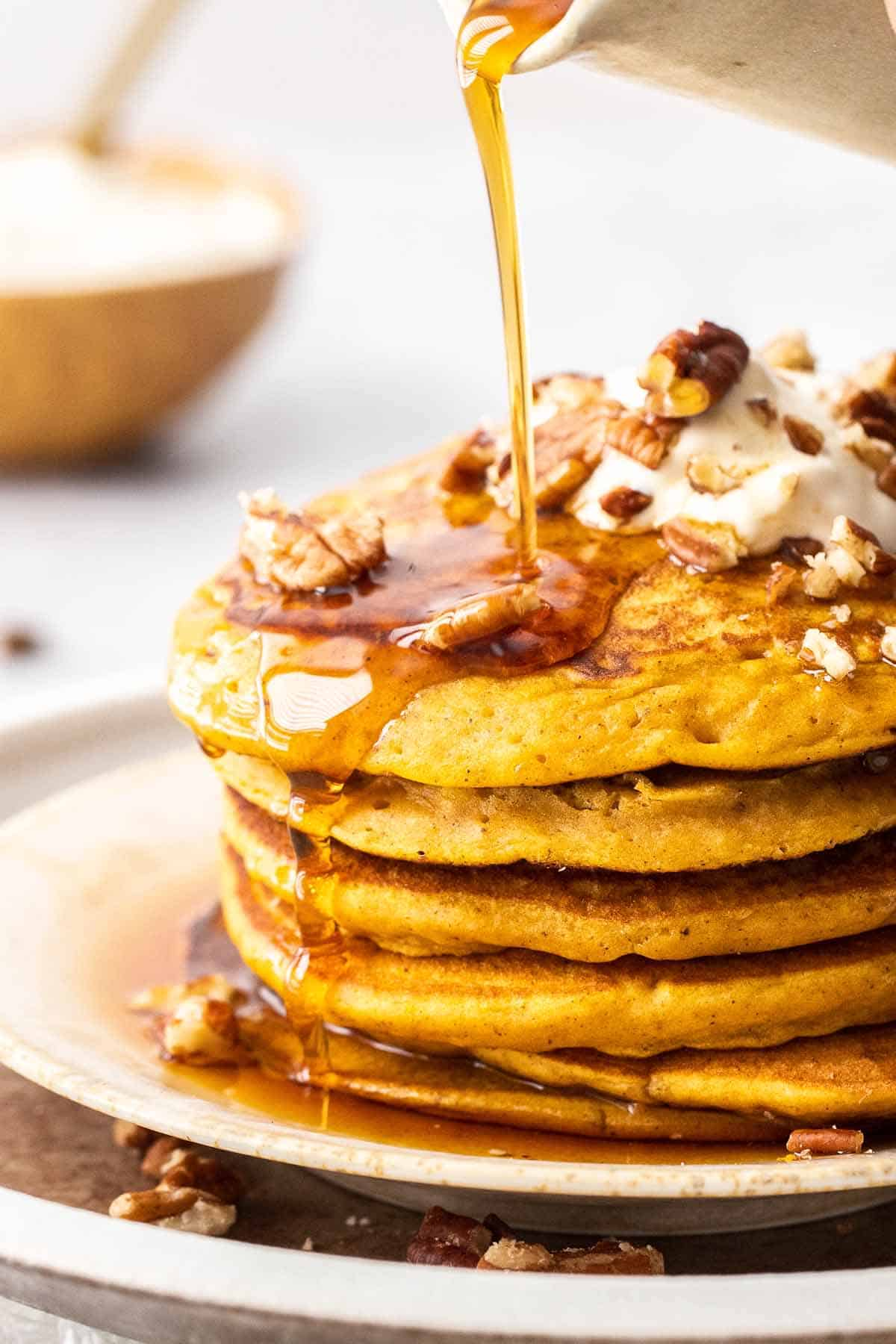 stack of pumpkin pancakes with poured syrup and pecans