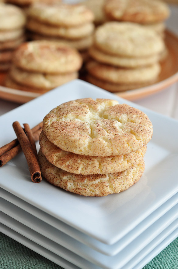 Three snickerdoodle cookies stacked on a stack of white square plates with more cookies in the background