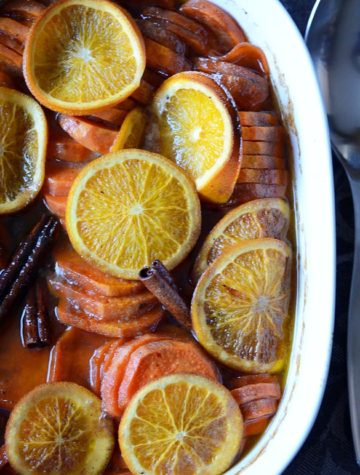 sliced candied yams with orange slices and cinnamon sticks