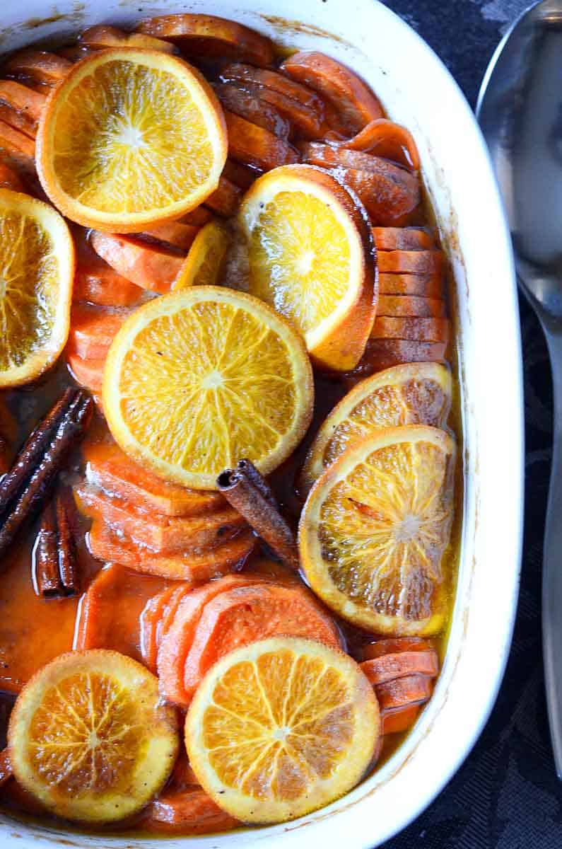 dish of candied yams with orange slices and cinnamon sticks