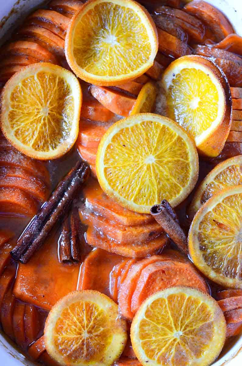 sliced sweet potatoes with orange slices and cinnamon sticks