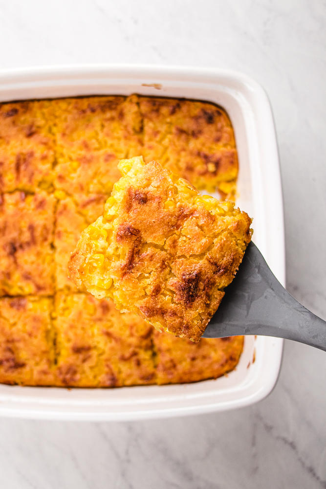 A scoop of corn casserole from a pan.