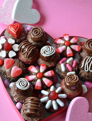 heart shaped box full of decorated cupcakes and candies