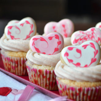 strawberry cupcakes topped with sugar cookie hearts