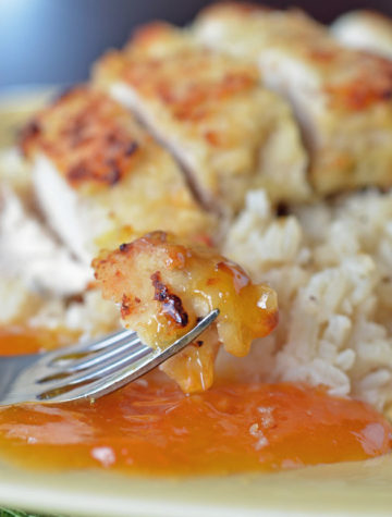 A fork with coconut crusted chicken with apricot sauce on a plate with rice.