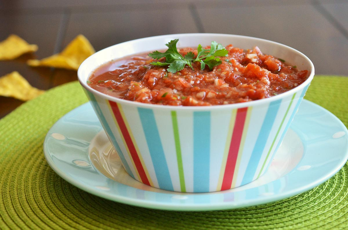 colorful bowl of fresh salsa with chips in background