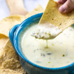 Chip dipped into Mexican white cheese dip.