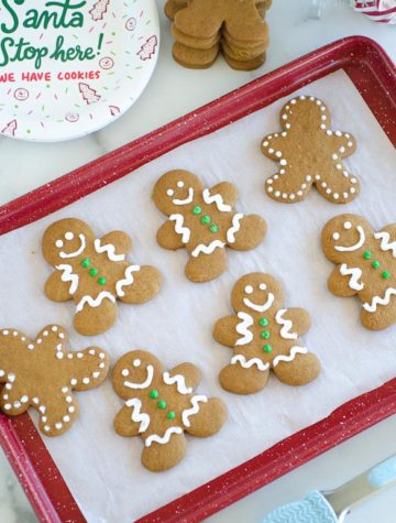 decorated gingerbread man cookies on a baking sheet for santa