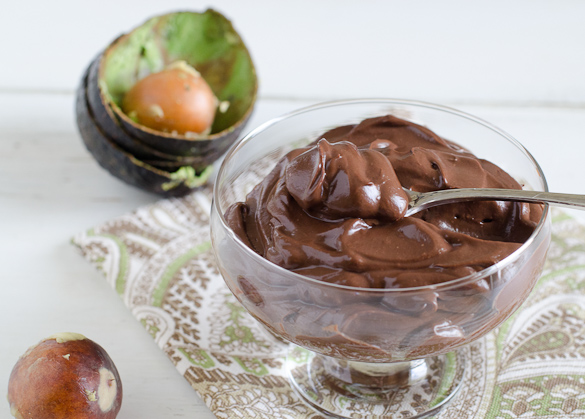 Small bowl of chocolate pudding with pitted avocado in background