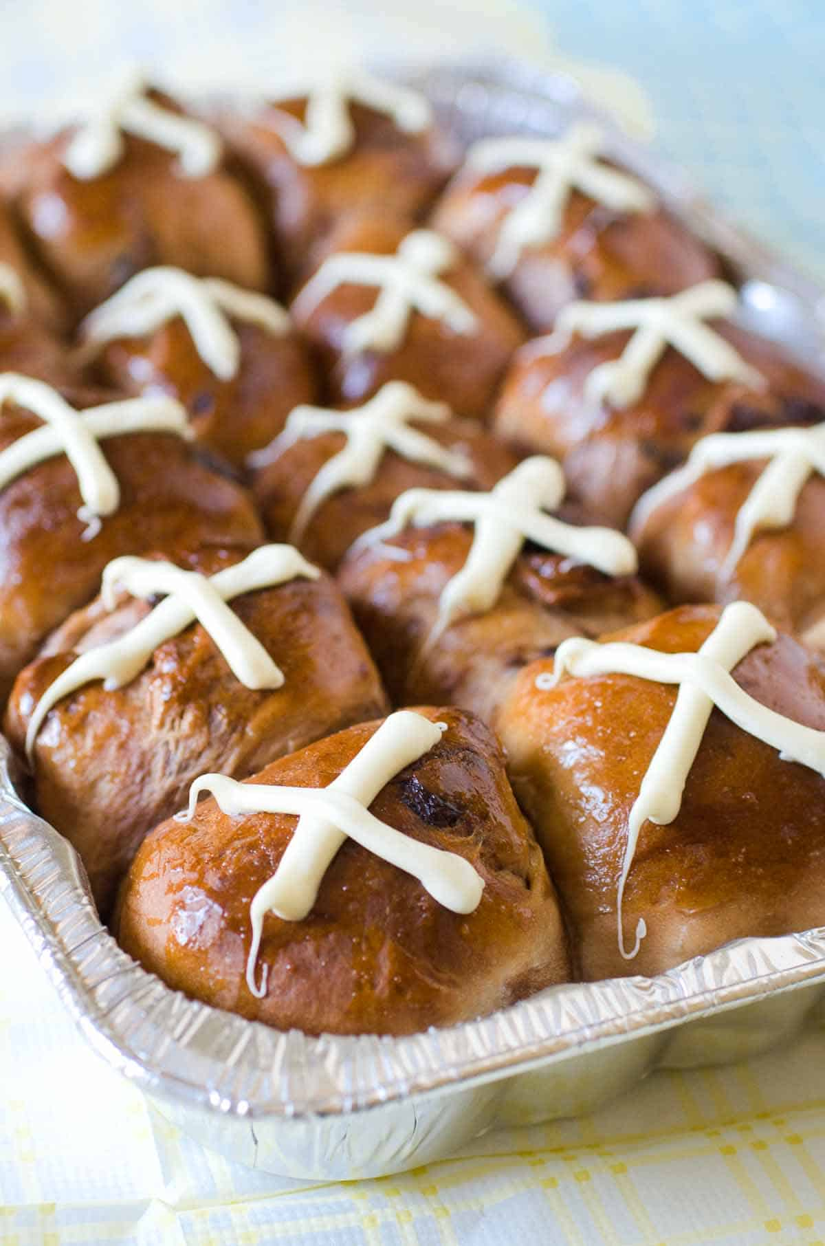 a pan of hot cross buns with white chocolate cross on top