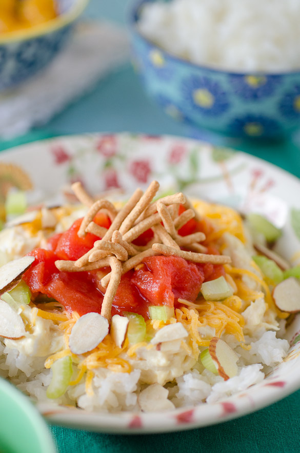 Bowl of stacked rice, almonds, tomatoes and chow mein noodles