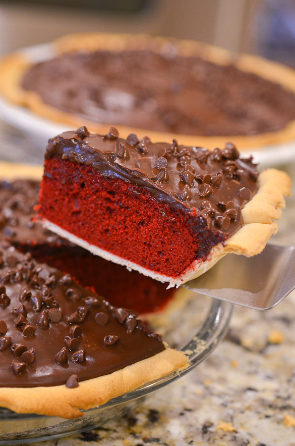 A slice of red velvet cake in a pie pan with chocolate chip topping