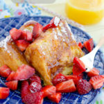 Slices of Angel Food Cake French Toast with strawberries and styrup on a blue plate.