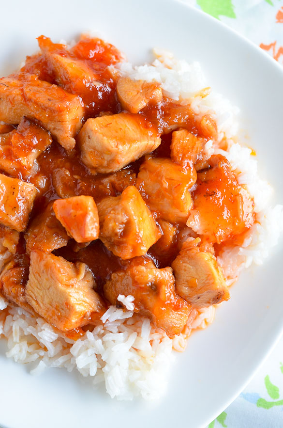 Sweet and sour chicken over white rice on a white plate