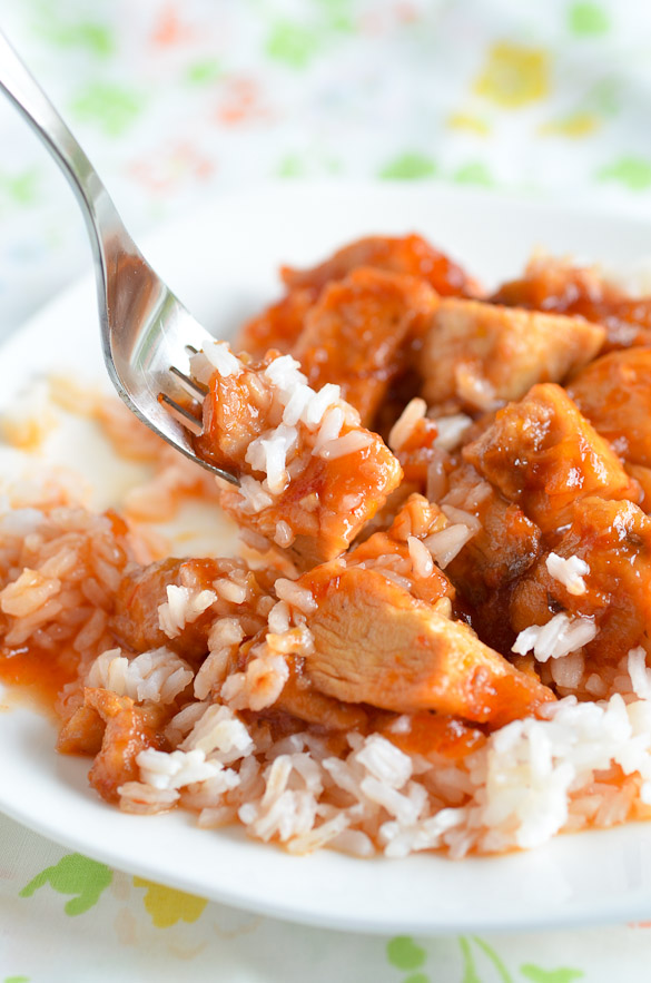 A fork with sweet and sour chicken over white rice on a white plate