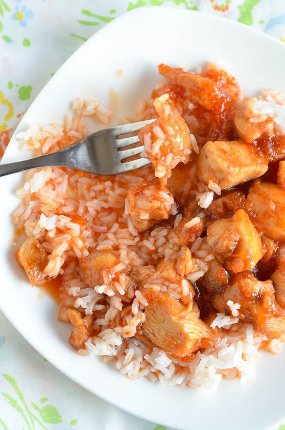 A fork with Sweet and Sour Chicken and white rice on a white plate
