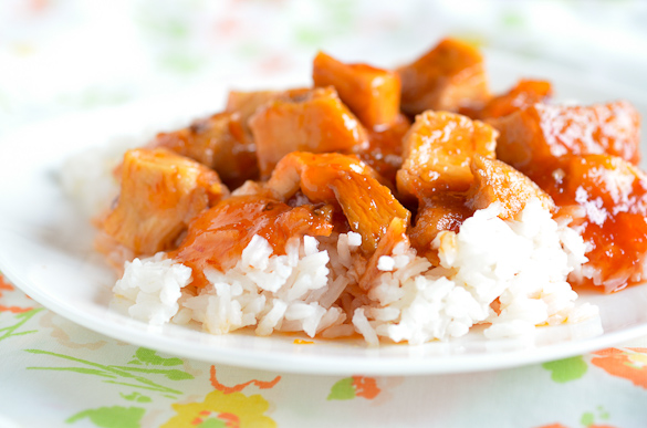 Sweet and sour chicken over rice on a white plate