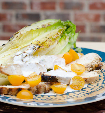 Plate of chicken salad with ranch dressing and yellow tomatoes.