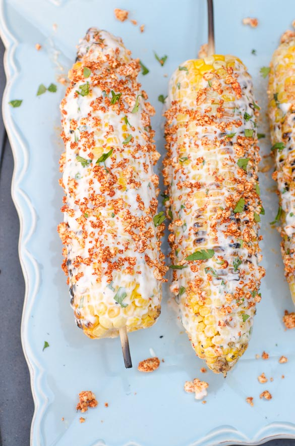 Mexican Street Corn - Mexican style corn on the cob smeared with a creamy spread and sprinkled with a cheesy spiced topping.