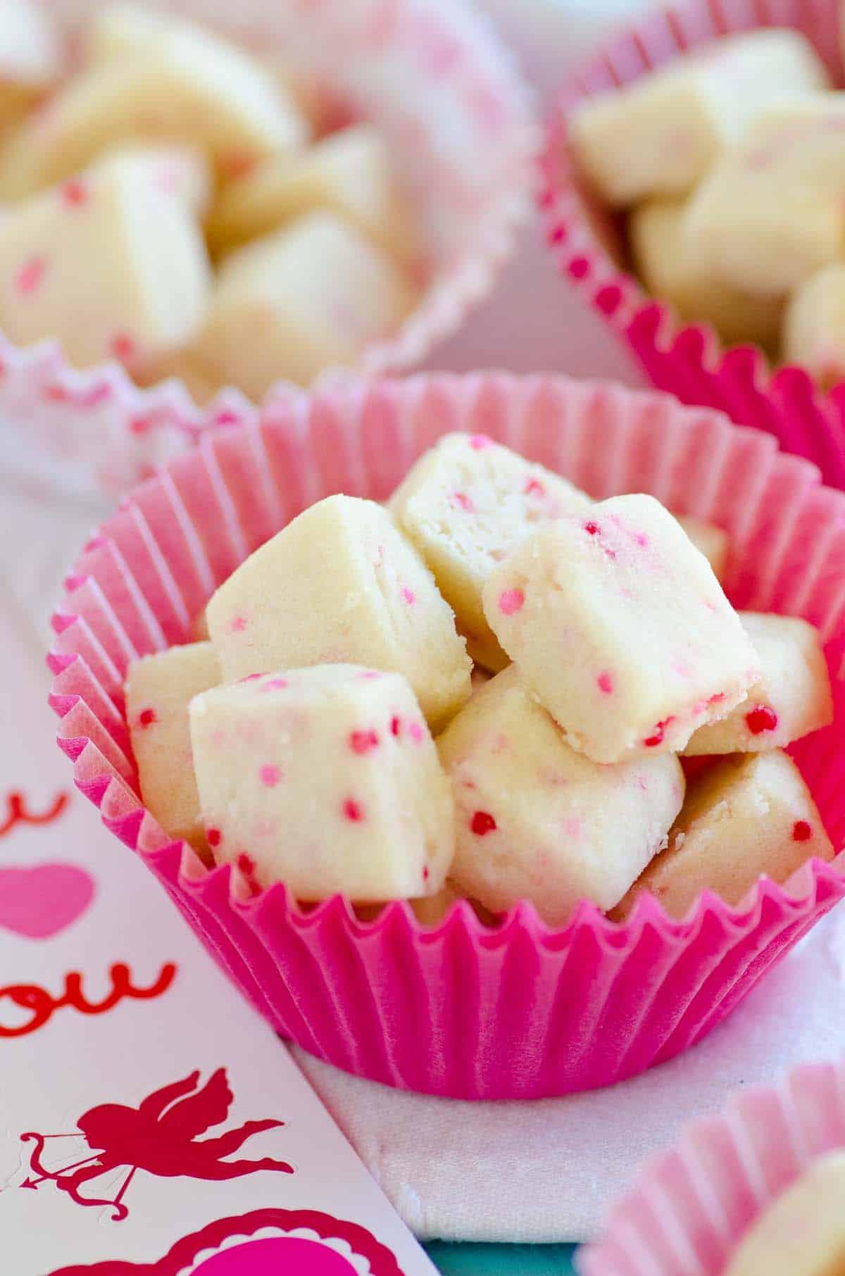 shortbread bites with red sprinkles in pink cupcake liner