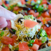 Seven Layer Dip Recipe - The easiest and quickest Mexican dip recipe with layers of refried beans, guacamole, taco seasoned sour cream and more!