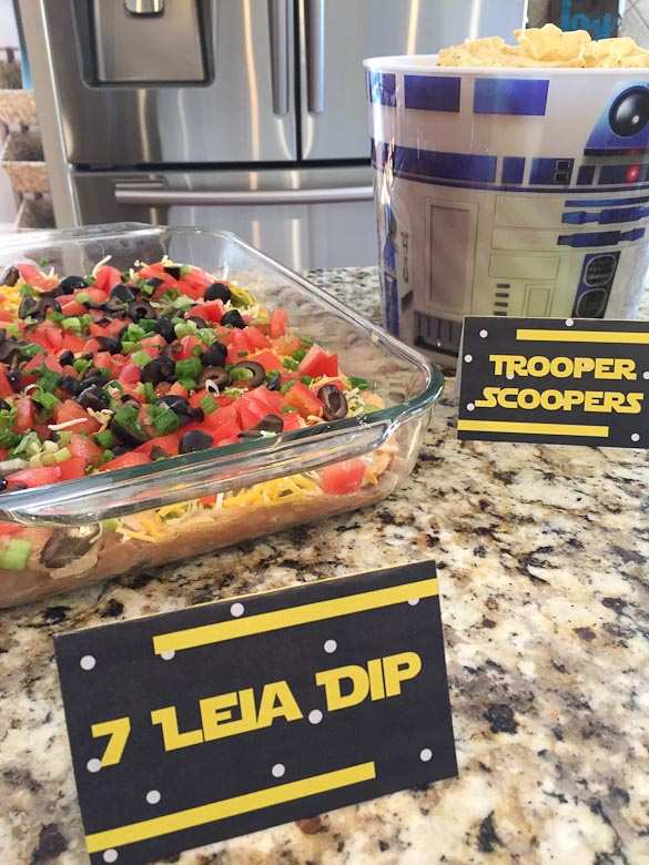 This Seven Layer Tex Mex Dip is EASY and a QUICK appetizer for any party year-round. A Mexican dip with layers of refried beans, guacamole, sour cream, black olives, tomatoes and cheddar cheese. Serve with scoop chips, crackers or veggies.