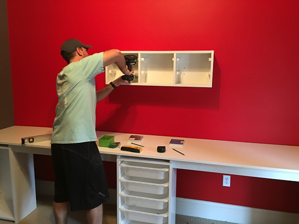 Man drilling shelves on red wall above desk.