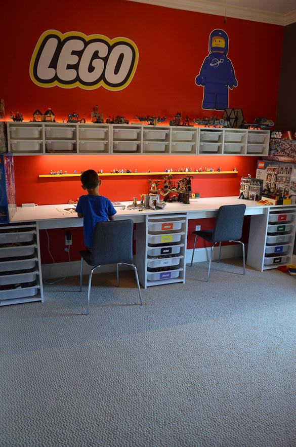 Child sitting and building LEGO set in his LEGO room