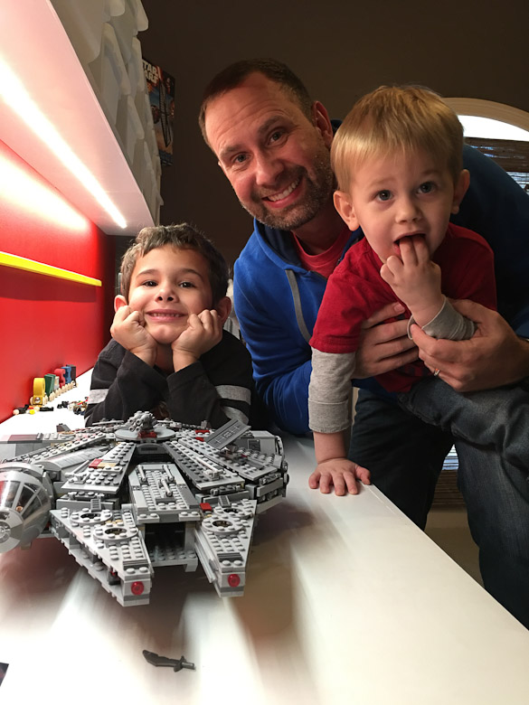 Dad and young sons with LEGO star wars millenium falcon set.