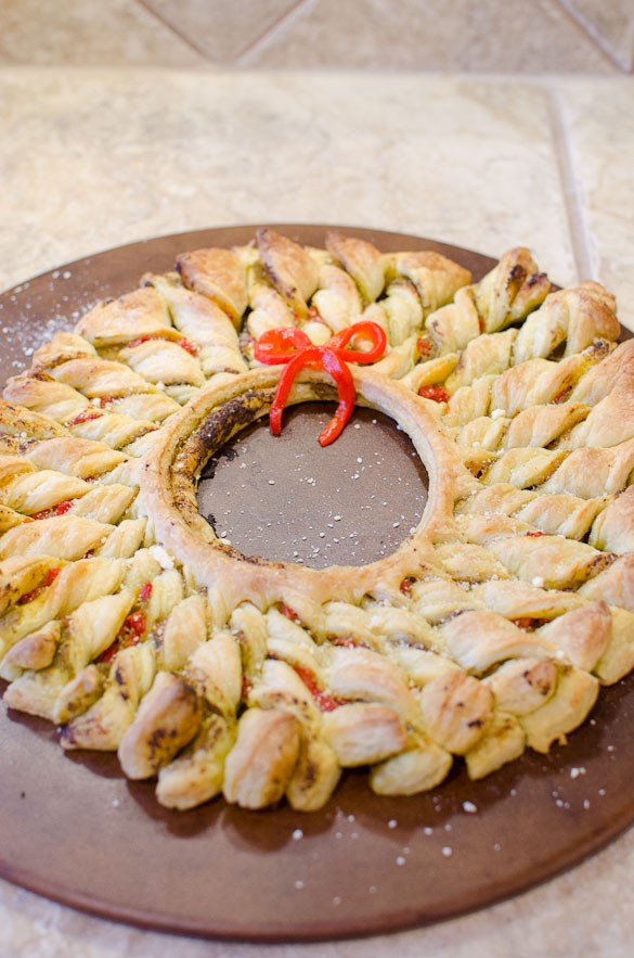 This Puff Pastry Pesto Wreath is the perfect easy appetizer for your holiday party. This delicious pastry wreath looks fancy, but it's quick and takes only 10 minutes to put together.