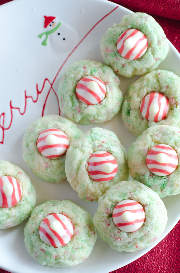 Sugar Cookie Candy Cane Blossoms are peppermint sugar cookies topped with Hershey's Candy Cane Kisses. They are a spin-off of the traditional peanut butter kiss blossoms. You will love these Candy Cane Blossom cookies because they are easy to make, delicious to eat, and perfect for your Christmas cookie swap!