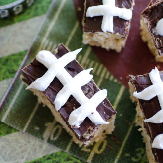 With just a few ingredients you can make these Football Chex Cereal Treat Bars for game day. Melted marshmallows are mixed with Chex cereal and topped with a simple melted chocolate. Use white icing to pipe on the football stripes to complete the decoration!