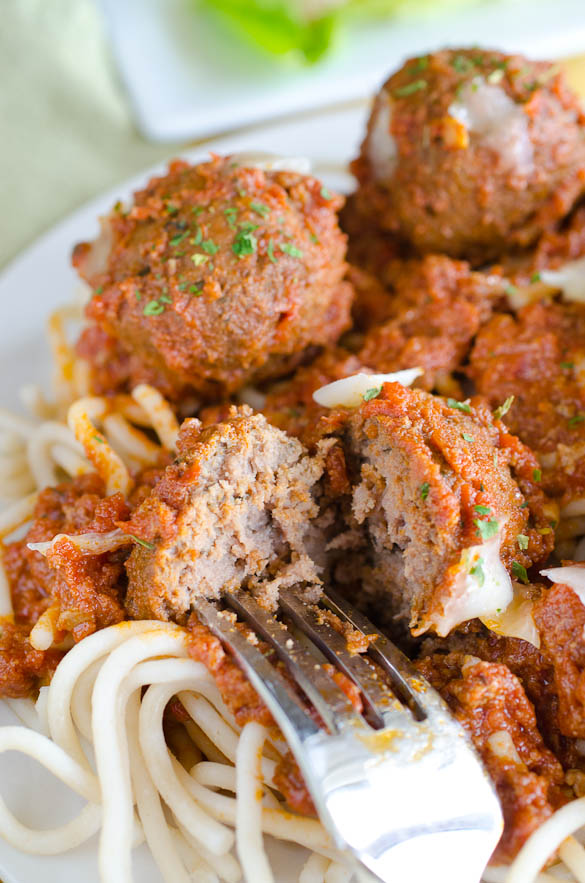 A fork cutting into spaghetti and meatballs on a plate.