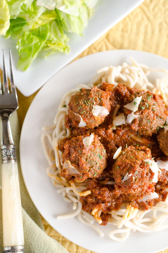 Spaghetti and meatballs with a fork and salad.