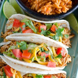 Three chicken tacos on a plate with spanish rice
