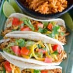 overhead of chicken tacos in flour tortillas and toppings