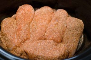 chicken breasts in bowl of crock pot sprinkled with taco seasoning