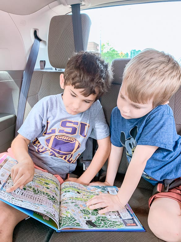 Kids reading book in car
