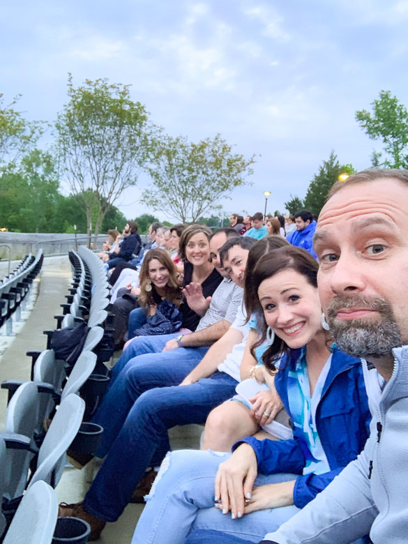 Friends sitting in a row of seats at the Brandon Amphitheater