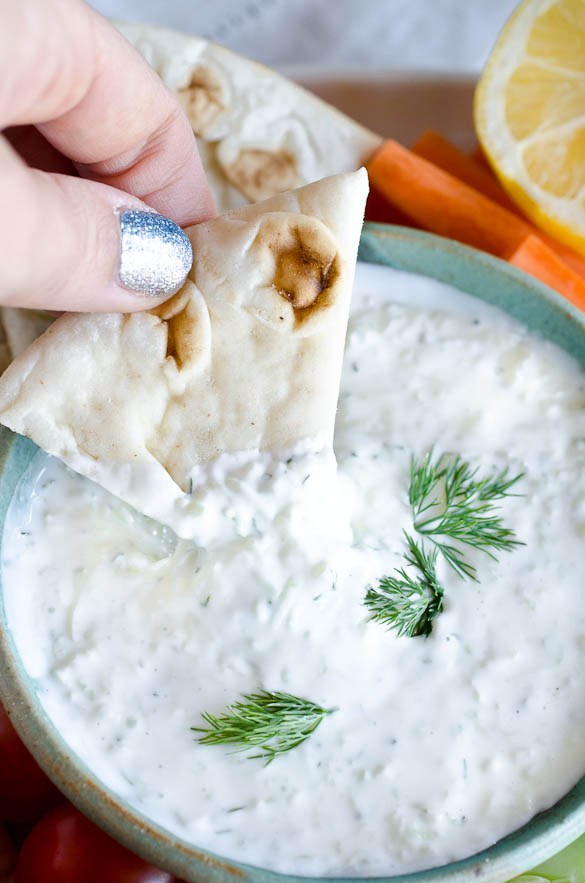 Pita wedge dipped in bowl of tzatziki sauce.