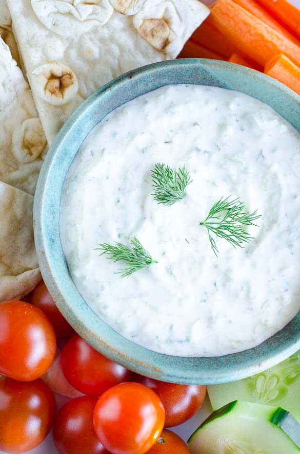 Vegetables around a bowl of tzatziki sauce.