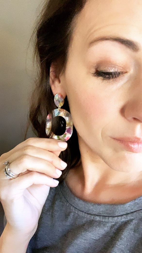 Woman wearing floral geometric earrings.