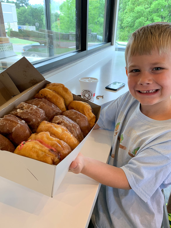 Little boy holding box of donuts.