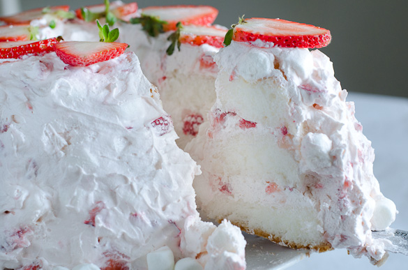 Slice of layered angel food cake with strawberry marshmallow frosting.
